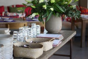 houten tafel met witte bloemen, borden, glazen, bestek en menukaarten