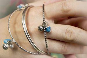 hand met armbanden, zilver en blauwe details
