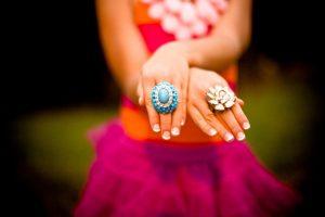 dame in roze kleding met handen vooruit met twee grote ringen