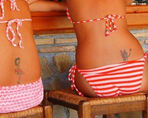 tatoeage op rug boven rood wit gestreepte bikini