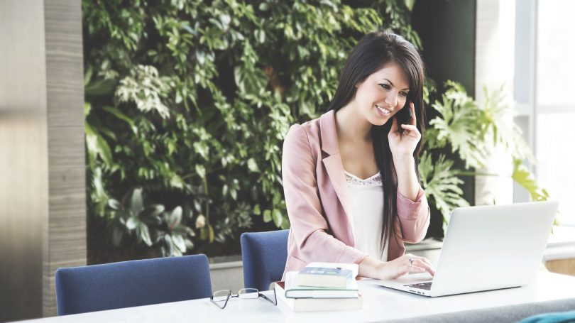 dame aan bureau met telefoon in handen