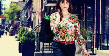 dame in fleurige top loopt door winkelstraat