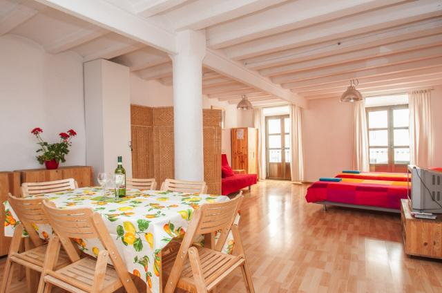 interieur appartement met houten meubilair, hoog plafond en ramen