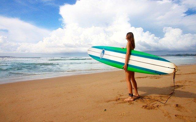 meisje met groene surfplank op strand