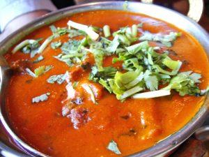 pan met gerecht in tomatensaus en verse groente bovenop