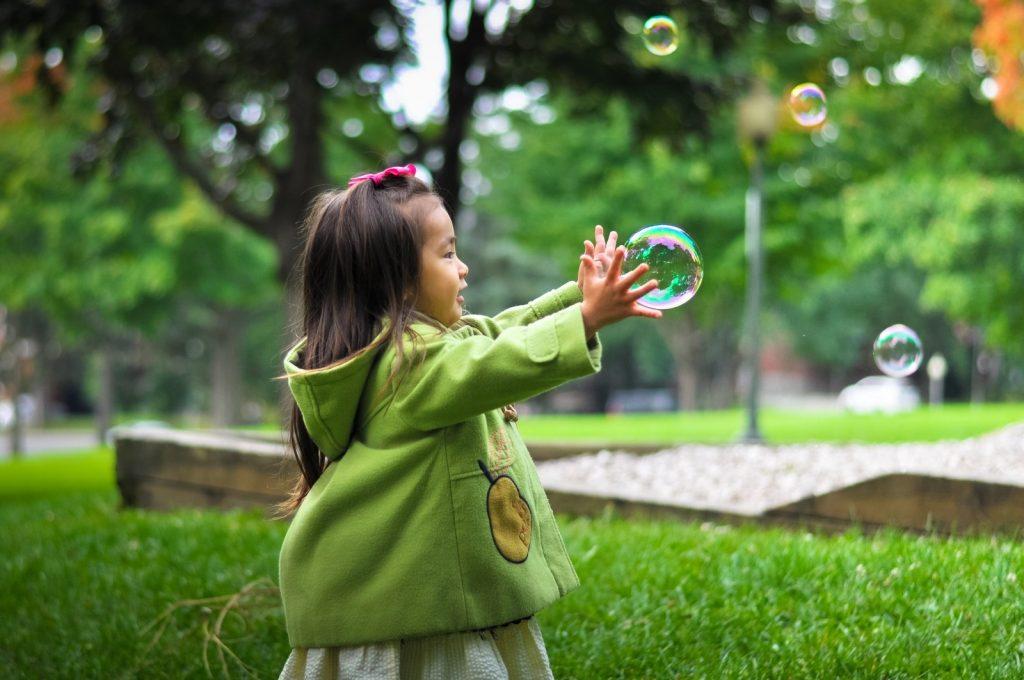 kind grijpt naar bellen van bellenblaas