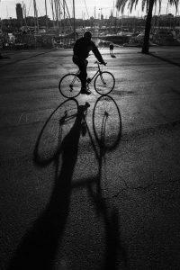 fietser en schaduw in haven barcelona