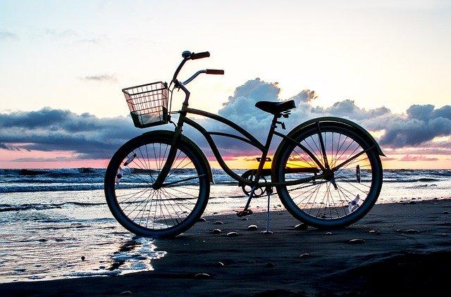 fiets op strand bij ondergaande zon