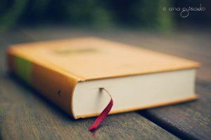 geel boek met rood lint erin op een houten tafel