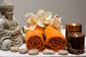 boedha, oranje handdoeken, bruine kaarsen, stenen en orchidee