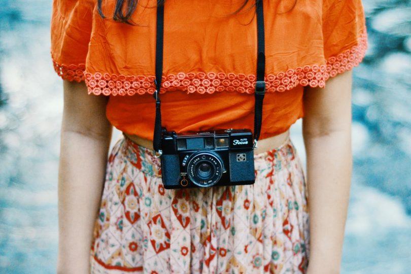 bovenlichaam van vrouw in oranje shirt met camera op de buik