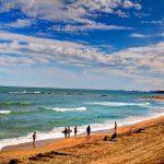 kust met surfers op het strand