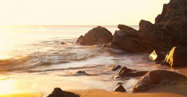 rotsen aan zee met zonsondergang