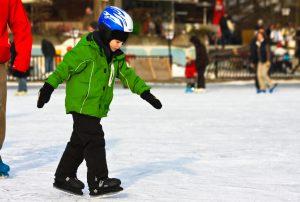 kind in groene jas op schaatsen