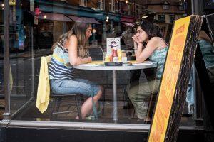 twee dames zitten aan tafel in cafe bij te kletsen