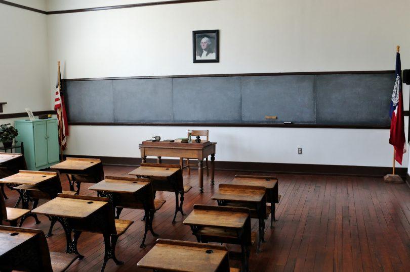 klaslokaal met schoolbord en tafels en stoelen