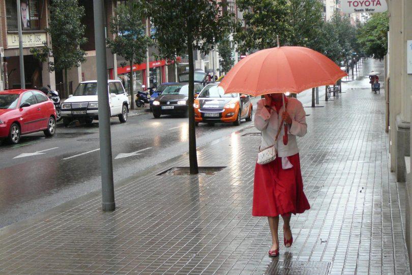dame in rode rok met paraplu in regen in barcelona