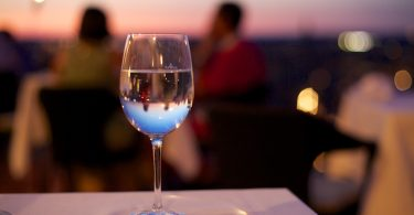 glas wijn op tafeltje in restaurant met ondergaande zon