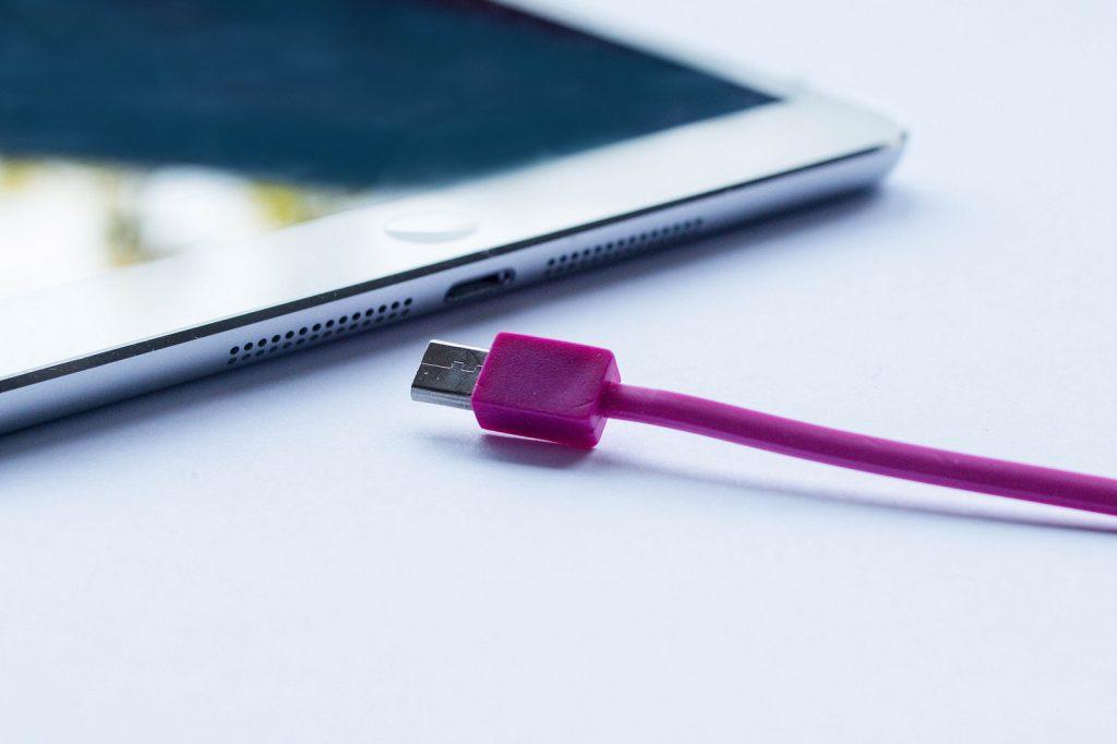 close up van ipad met paarse lightning kabel
