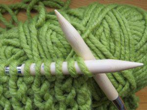 breinaalden met groene garen