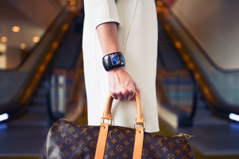 net geklede dame met blauwe armband en tas