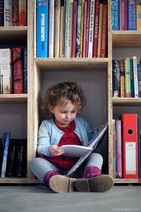 kind met veel boeken om zich heen leest in boek