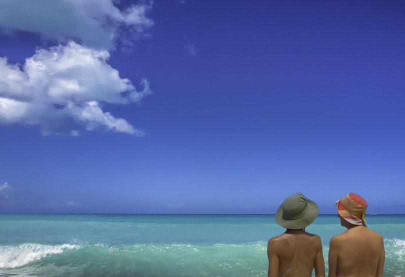 twee personen met hoed aan zee met blauwe lucht