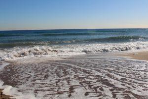 golf stroomt terug van strand naar zee