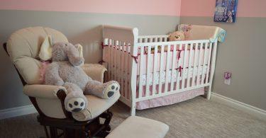 babykamer met bed stoel roze behang