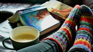 wollen regenboogsokken met boek en kop koffie