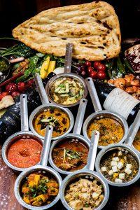 acht kleine pannetjes met diverse indiase gerechten en naan