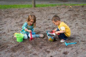 twee jonge kinderen spelen buiten in zandbak