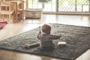 klein kind op vloerkleed met trommel