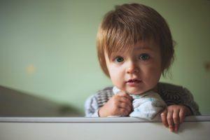 klein kind staat aan rand van ledikant