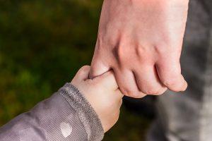 kind houdt vinger ouder vast