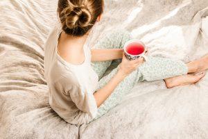 vrouw in pyjama op bed met kop thee