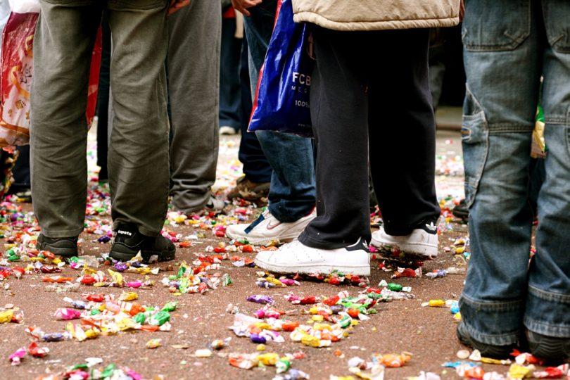 straat met mensen en snoepgoed op de grond