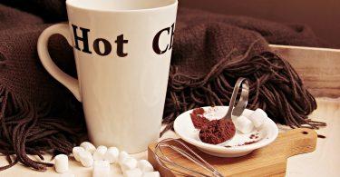 beker warme chocolademelk met lepel cacao