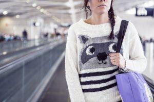 vrouw met paarse tas onderweg naar gate op vliegveld