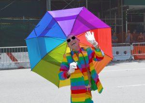 man op straat in regenboogpak met witte handschoenen, zonnebril en regenboogparaplu