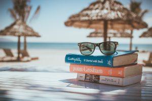 stapeltje leesboeken met zonnebril op strand