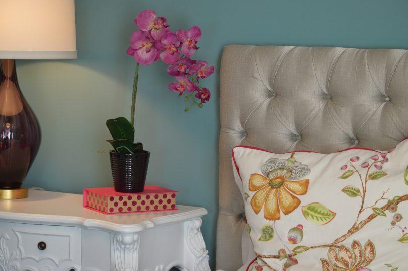 bed met orchidee op nachtkastje