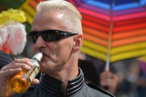 man met zonnebril en flesje bier voor regenboogkleuren parasol