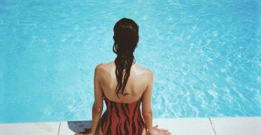 vrouw zit aan rand zwembad
