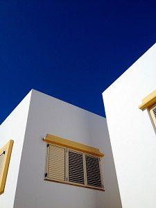 wit appartement met gele luiken tegen blauwe lucht