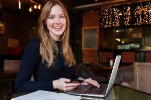 lachende vrouw met telefoon en laptop