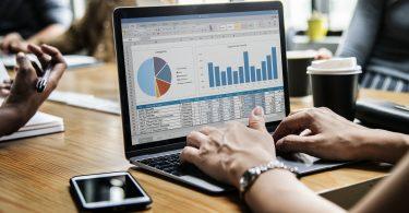financiele overzichten op computer met persoon aan het typen