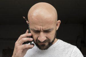 kale man met baard aan telefoon