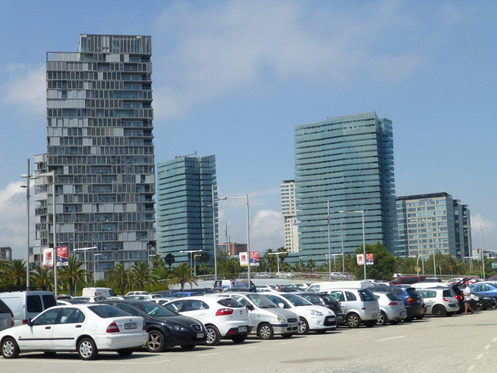 hoge flatgebouwen met grote parkeerplaats op voorgrond