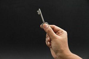 sleutel tussen duim en wijsvinger en zwarte achtergrond
